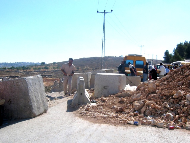 The process: We took an Israeli servisse onto an Israeli bypass highway to a dirt road; we got out and climbed over the Israeli army\'s manmade concrete and dirt roadblock where we boarded a Palestinian servisse to take us over narrow, rutted dirt roads into the beautiful village of Biddu.